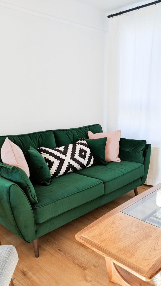 Ghế sofa màu ngọc lục bảo và những chiếc gối in tạo nên sắc màu tươi sáng.