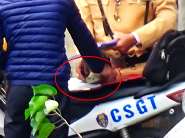 CSGT Hà Nội nhận một tờ nghi là tiền từ một người vi phạm giao thông - Ảnh cắt từ clip