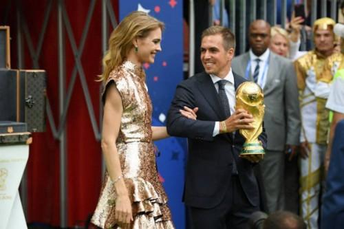 Siêu mẫu Nga Natalia Vodianova (trái) tiến ra sân khấu cùng cựu đội trưởng tuyển Đức vô địch World Cup 2014 - Philipp Lahm. Hai người mang theo chiếc cúp vàng của giải đấu năm nay.