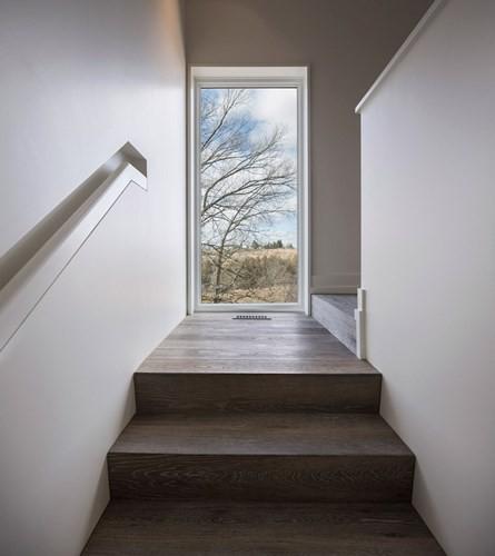 Bậc cầu thang nối thẳng đến những khung cửa lớn, giống như mở ra một không gian khác bên ngoài.