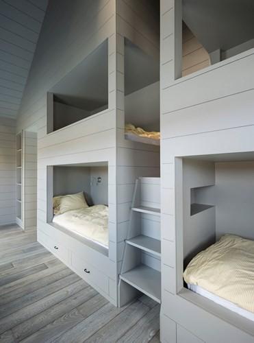 Trong nhà còn bao gồm nhiều phòng ngủ và cả phòng giải trí. Những giường tầng bố trí để khi nhà có khách hoặc đông trẻ với tông màu trắng xám, dễ chịu.