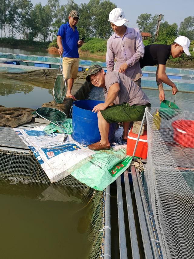 Anh Dương Việt Anh (người ngồi) cùng công nhân phân loại và kiểm tra tình trạng của cá nuôi theo định kỳ. Ảnh: Hoàng Huyền