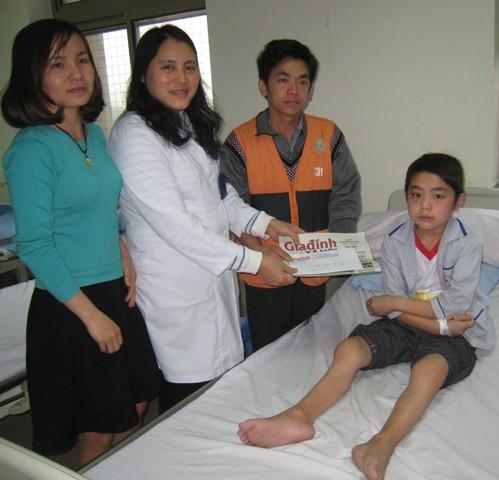 Bé Vừ Mí Pó nhận quà của độc giả Báo Gia đình & Xã hội ở Viện Huyết hoc Truyền máu Trung ương.