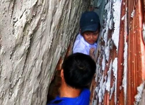 Cháu bé được cảnh sát phá tường giải cứu. Ảnh: Thanh Liêm.