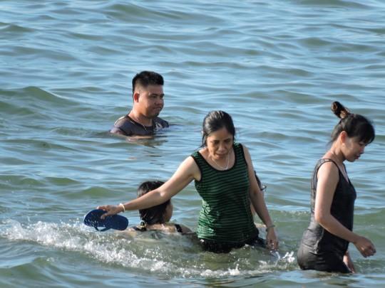 Du khách dùng dép để gạt sứa biển ra khỏi khu vực đang tắm