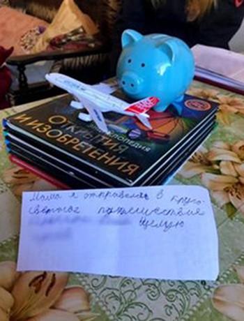 Tư trang mà cậu bé Nga mang theo trong chuyến đi vòng quanh thế giới và bức thư để lại cho mẹ. Ảnh: BBC