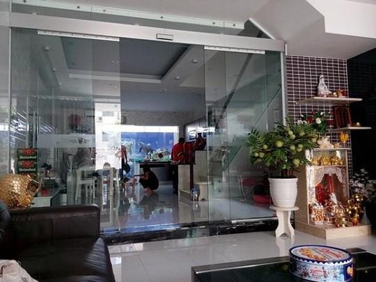 Phòng khách được thiết kế rộng rãi, sáng rực với tông màu trắng và nội thất sáng màu. Cửa ra vào chính và lan can cầu thang đều được thiết kế bằng kính trong suốt.