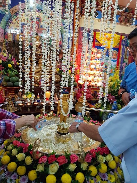 Rất nhiều người lấy nước tắm Phật về vẩy cho mọi người cùng may mắn.
