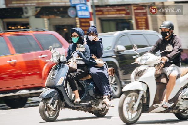 Nhiệt độ ngoài đường tại Hà Nội lên tới 50 độ C, người dân trùm khăn áo kín mít di chuyển trên phố - Ảnh 1.