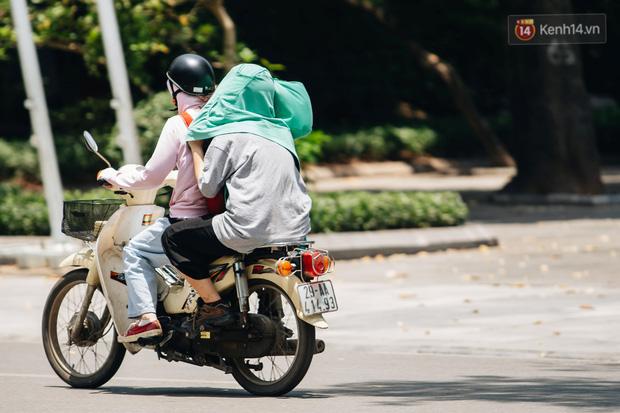 Nhiệt độ ngoài đường tại Hà Nội lên tới 50 độ C, người dân trùm khăn áo kín mít di chuyển trên phố - Ảnh 4.