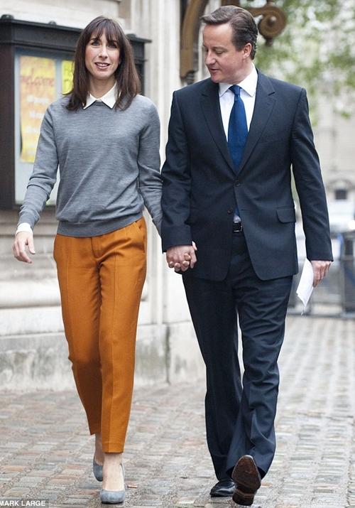 Hai vợ chồng Thủ tướng sánh bước, trong khi ông David Cameron lịch lãm với vest thì Phu nhân diện quần ống đứng Zara cùng áo chui đầu của hãng thời trang đường phố Cos và giày xám LK Bennett.