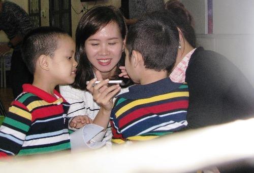 Hai cháu nhỏ này thích thú khi nhìn thấy chiếc điện thoại. Ảnh:Minh Cương
