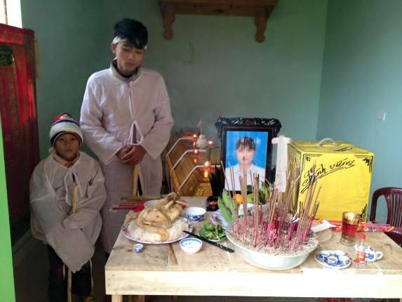 2 người con trai đứng trước bàn thờ mẹ