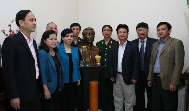 Bộ trưởng Nguyễn Thị Kim Tiến cùng các lãnh đạo Bộ Y tế, đại diện các Cục, Vụ, đơn vị thuộc Bộ chụp ảnh cùng bức tượng đồng khắc chân dung cố Bộ trưởng Vũ Văn Cẩn