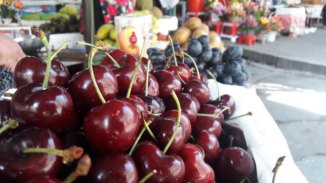 Tại chợ Tân Định, cherry bày bán gần lề đường, giữa trời nắng vẫn tươi ngon.