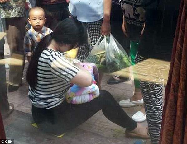 Người phụ nữ này không ngần ngại vén áo cho em nhỏ bú khi nghe bé khóc vì khát sữa. Ảnh: CEN.