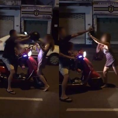 Người vợ dùng mũ bảo hiểm đánh liên tiếp về phía người chồng, mặc cho con gái nhỏ ngồi ngay phía trước. Ảnh cắt từ clip.