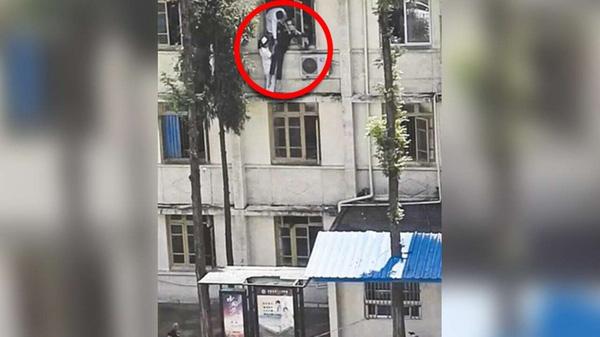 Để cứu một bệnh nhân có ý định nhảy lầu tự tử, một nữ y tá đã liều mình trèo hẳn ra ngoài khung cửa sổ, đứng vắt vẻo trên cao.