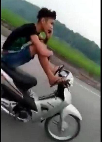 Nam thanh niên điều khiển xe máy bằng 2 chân, tay cầm điện thoại khoe với mẹ đang lái xe an toàn - Ảnh cắt từ clip