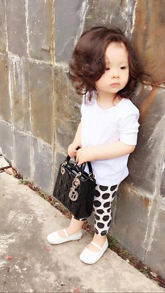 Trong một hình ảnh street style, bé Mộc Trà mặc bộ đồ như fashionista thứ thiệt với quần họa tiết chấm bi, áo trắng, giày trắng. Chiếc túi Lady Dior của bé có giá trị khoảng hơn 60 triệu đồng.