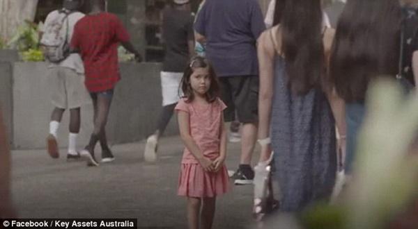 Một bé gái cũng đứng một mình, bộ dạng lo lắng như vừa lạc mất cha mẹ.