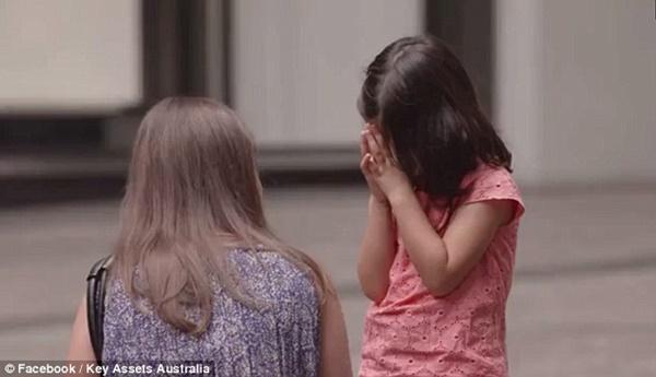 Một người phụ nữ dừng lại hỏi thăm khi thấy bé gái vùi mặt vào tay.
