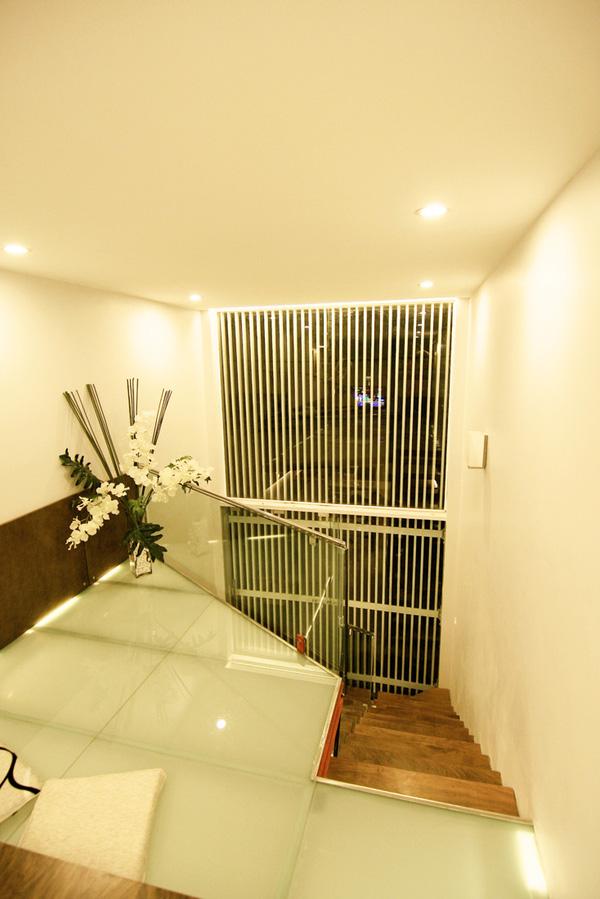 Cầu thang cốn thép mặt gỗ dẫn lên tầng lửng, là nơi đặt phòng khách và phòng ngủ.