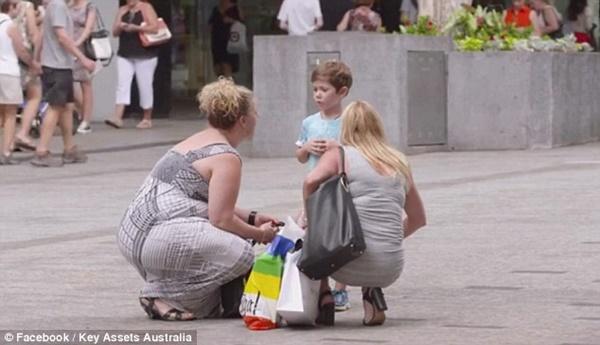 Hai người phụ nữ đang đi mua sắm dừng lại hỏi chuyện bé trai.