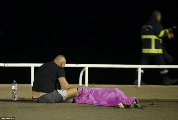 Một người đàn ông vô cùng đau đớn bên xác người thân của mình. Sự việc xảy ra quá nhanh và quá kinh hoàng.