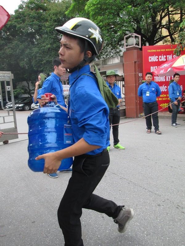 Sinh viên tình nguyện hối hả bê nước phục vụ thí sinh.