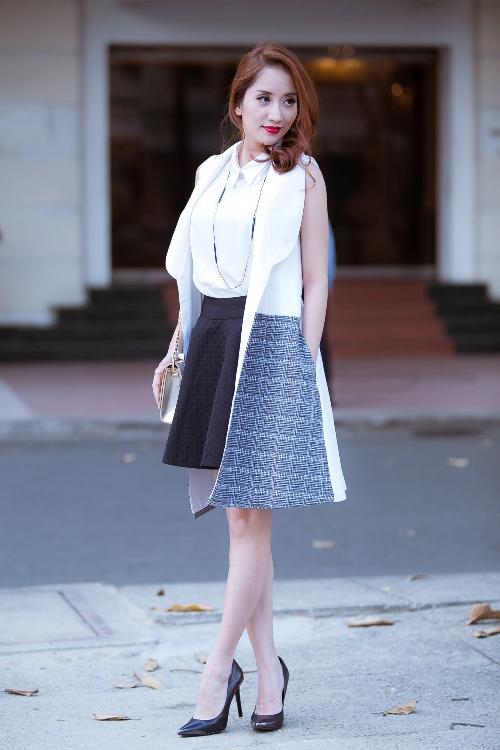 Váy xếp ly đen kết hợp áo sơ mi trắng cùng blazer dáng dài không tay khiến Khánh Thi trông trẻ trung hơn so với tuổi.