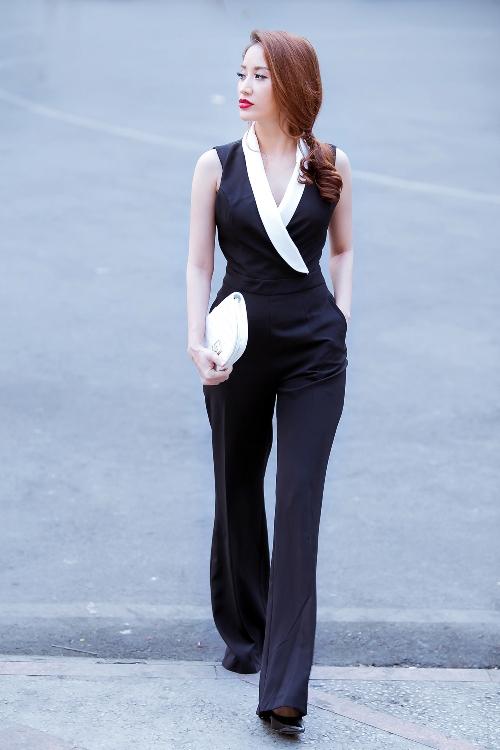 Bộ jumpsuit màu đen tôn vóc dáng và tạo hiệu ứng kéo dài chân cho bà mẹ một con. Cô chọn ví cầm tay màu trắng đồng điệu với chi tiết cổ áo.
