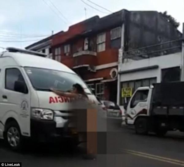 Người phụ nữ đứng chặn xe cứu thương.