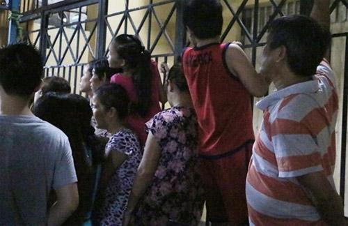 Nhiều người đứng trên ghế, trèo lên cổng hướng mắt về lễ viếng đang diễn ra bên trong.