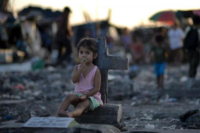 Một bé gái ngồi cạnh tấm bia mộ giữa một khu ổ chuột bên trong nghĩa địa ở thị trấn phố Navotas, thuộc thủ đô Philippines, ngày 29/10/2015.