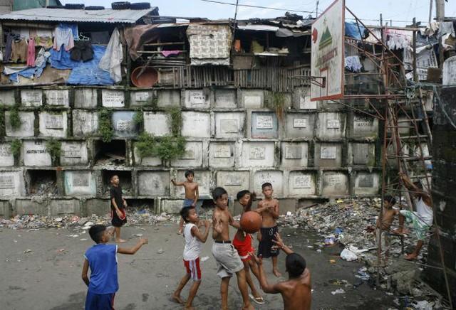 Các em nhỏ chơi bóng rổ trong nghĩa địa ở Manila ngày 21/10/2008.