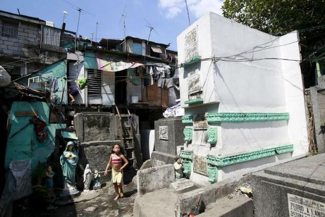 Những ngôi mộ bỏ hoang được người dân nghèo biến thành nhà ở. Ảnh: Bé gái đi bộ trước cửa nhà tại nghĩa trang nhân dân Nam Manila ở thành phố Pasay ngày 30/10/2015.