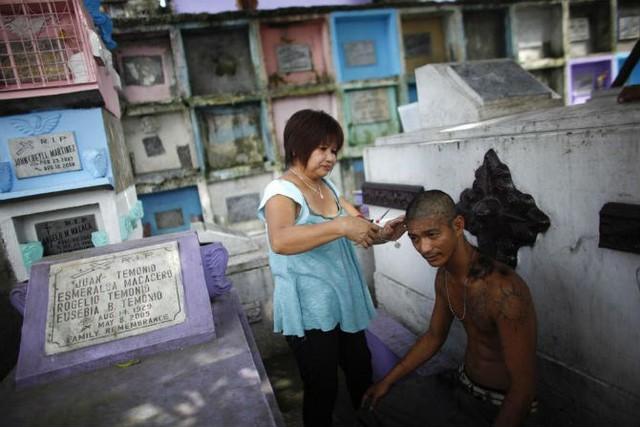 Người phụ nữ cắt tóc cho một người đàn ông trước một ngôi mộ trongnghĩa trang Bắc Manilangày 28/10/2011.