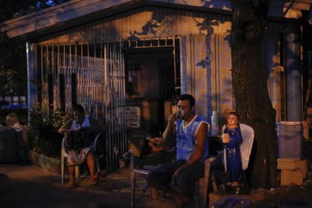 Người đàn ông bình thản uống cà phê vào lúc bình minh tại nghĩa trang Bắc Manila ngày 28/10/2011.