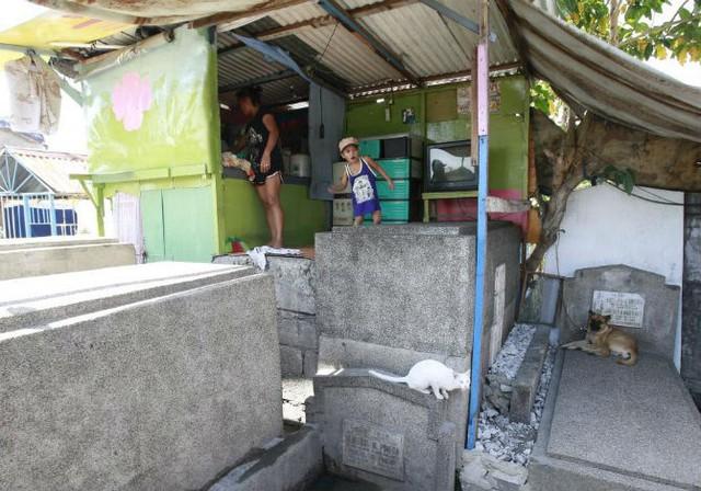 Ngôi nhà tạm bợ của một gia đình được xây dựng trên những ngôi mộ trong nghĩa trang nhân dân Nam Manila ở thành phố Passay trong vùng đô thị của Manila ngày 30/10/2015.