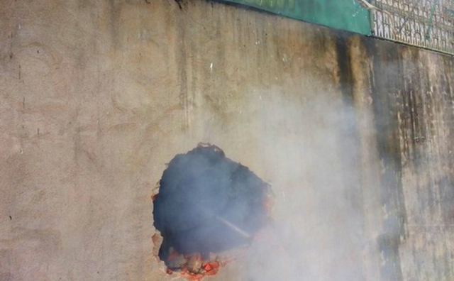 Các chiến sỹ chứa cháy phải đục lỗ để chui vào kho hàng dập lửa