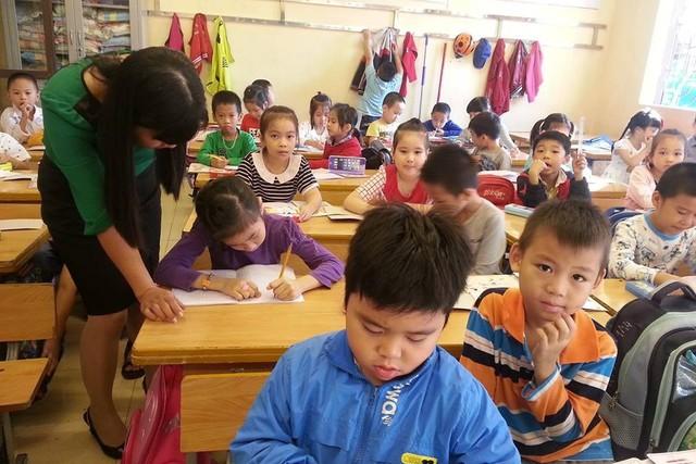 Cô giáo Nguyễn Thị Hằng hướng dẫn bé Vũ Hà An Thư viết bằng tay trái. Ảnh: M.Lý