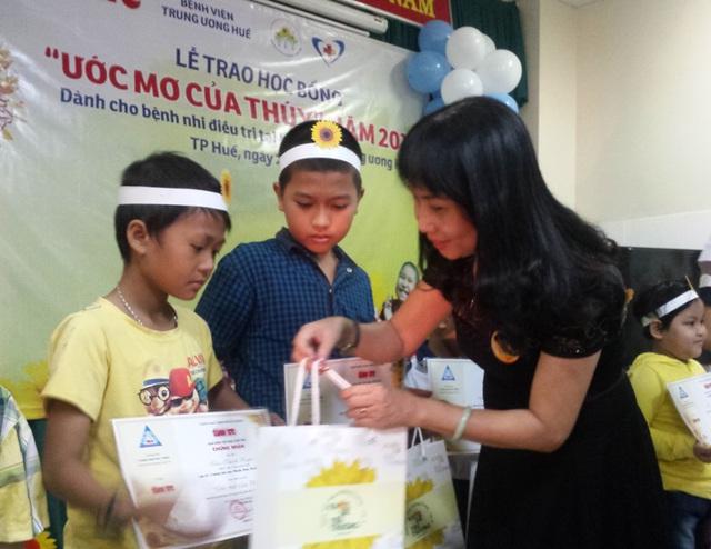 Đại diện Trung tâm bệnh nhi Bệnh viện Trung ương Huế trao học bổng cho các em. Ảnh Lê Chung