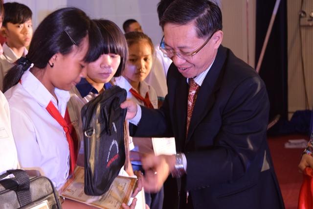 Ông Nguyễn Ngọc Hùng đang tặng quà cho các em học sinh.