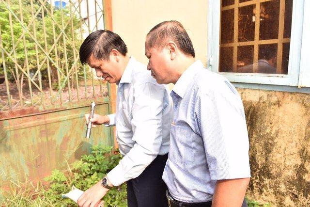 Thứ trưởng Y tế Nguyễn Thanh Long (trái) đang đổ nước trong lọ hoa chứa nhiều bọ gậy tại một hộ gia đình khi giám sát hoạt động phòng chống dịch bệnh sốt xuất huyết tại Đồng Nai sáng 18/9.