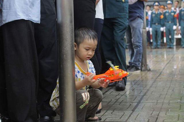 Một bé trai đang nghịch chiếc máy bay mô hình dưới trời mưa như trút nước ngoài sân nhà tang lễ khiến nhiều người xót lòng.