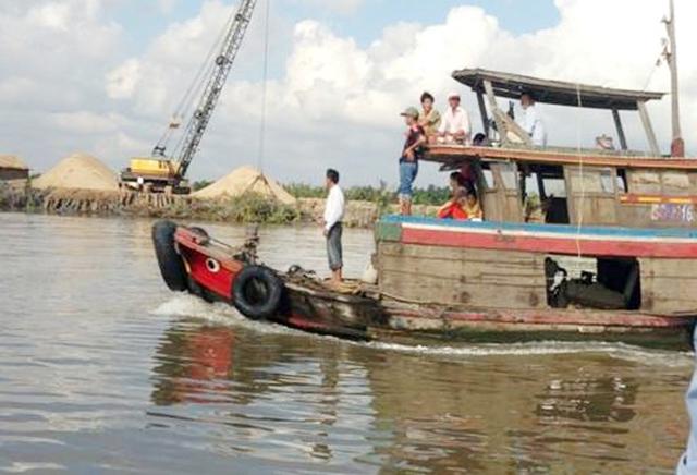 Người dân ven sông Soài Rạp hỗ trợ công an phương tiện và lưới để bắt cá sấu. Ảnh:Nhật Tân.