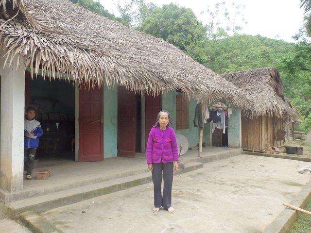 Bà Vi Thị Việt bên cạnh ngôi nhà xập xệ. Ảnh: N.Hưng