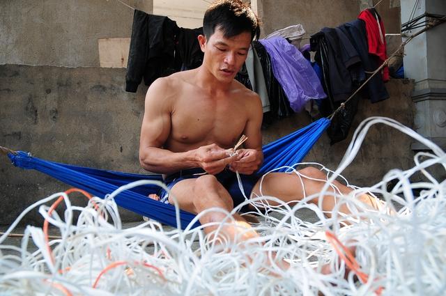 Anh Mai Xuân Lý đang ngồi đan lưới chờ ngày được trở lại biển.