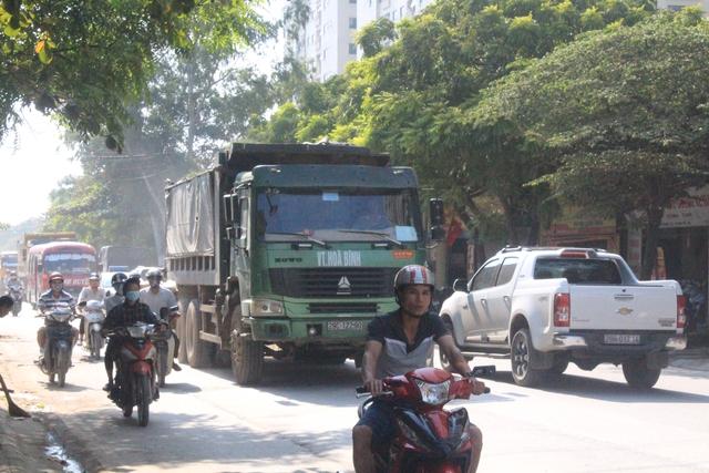 Xe tải hạng nặng lưu thông cùng với dòng người trên đường 70. Ảnh: Hà Phương